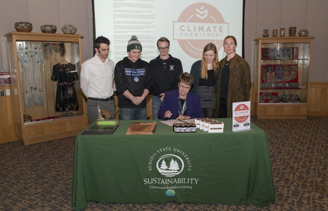 President Faith Hensrud signs Second Nature's Climate Commitment while Jordan Lutz, sustainability project manager, Connor Newby, student senate president, Corrie Stockman, student senate vice president, Anna Hayes, student senator and sustainability office employee and Erika Bailey-Johnson, sustainability coordinator, look on.