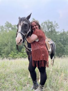 Abigail Dorey standing next to a horse in a field