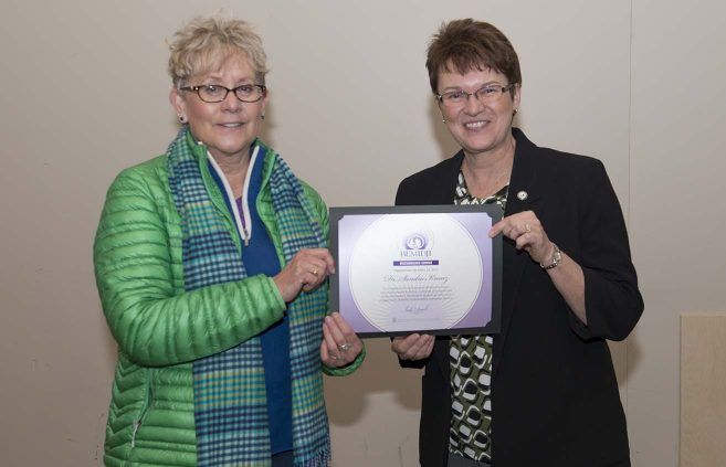 Dr. Sandra Kranz, professor of accountancy, receives BSU's Distinguished Service Award from President Faith C. Hensrud.