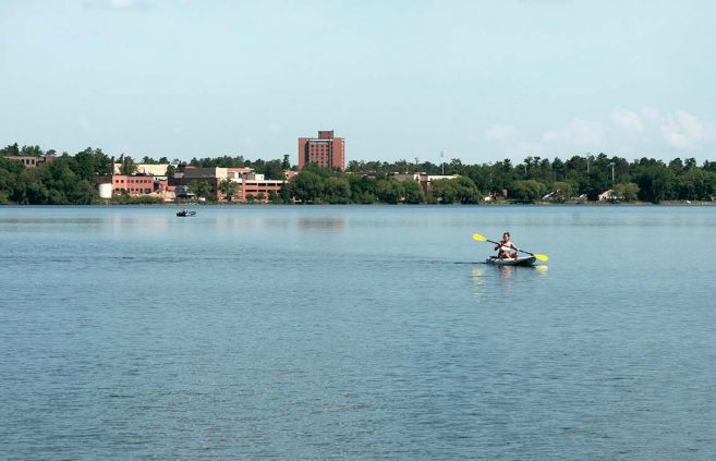A student uses a kayak rented from BSU's Outdoor Program Center to paddle Lake Bemidji in 2012.