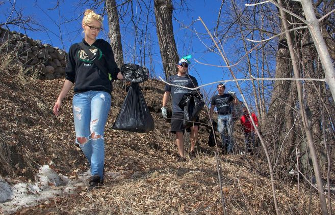 Students collect trash along the Lake Bemidji shoreline as part of Earth Day activities in April 2012.