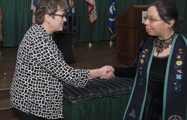 BSU President Faith C. Hensrud greeted graduating students after they received their stoles.