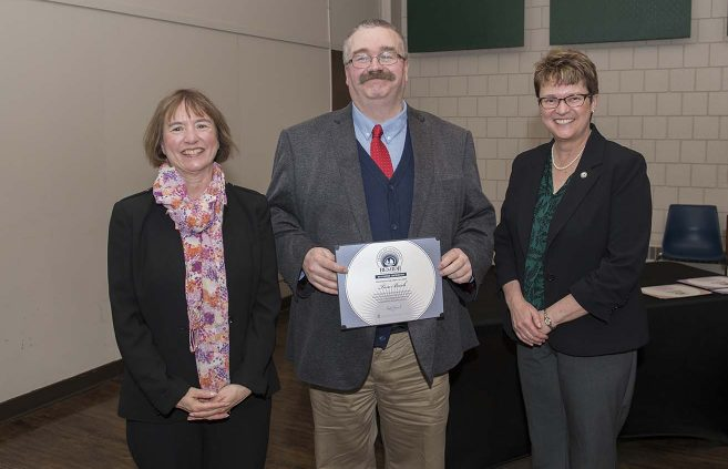 Dr. Tom Beech (center) won an Outstanding Contribution Award. He's pictured with VP Karen Snorek (left) and President Hensrud.