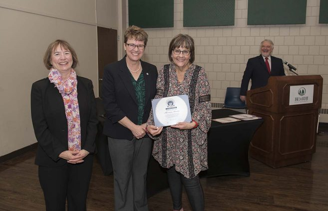 Mary Herried (right) accepted an Outstanding Contribution Award on behalf of Dr. Shannon Norman. She's pictured with VP Karen Snorek (left) and President Hensrud.
