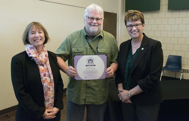 University photographer John Swartz (center) won a Distinguished Service Award. He's pictured with VP Karen Snorek (left) and President Hensrud.