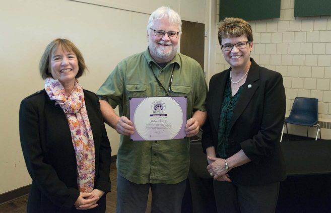University photographer John Swartz (center) won a Distinguished Service Award. He's pictured with VP Karen Snorek (left) and President Hensrud.