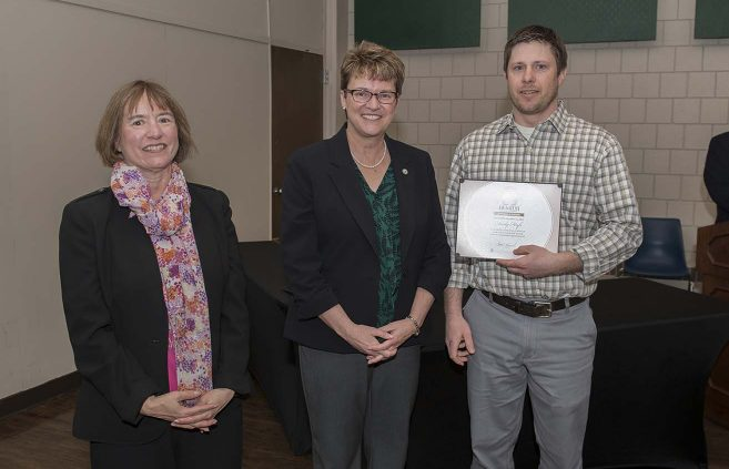 Dr. Andy Hafs, associate professor of biology (right), won the Excellence in Teaching Award. She's pictured with VP Karen Snorek (left) and President Hensrud.
