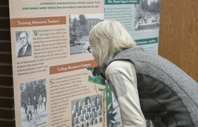Professor Emerita Mur Gilman examines one of the banners recapping a decade of BSU history on the pre-celebration History Walk.
