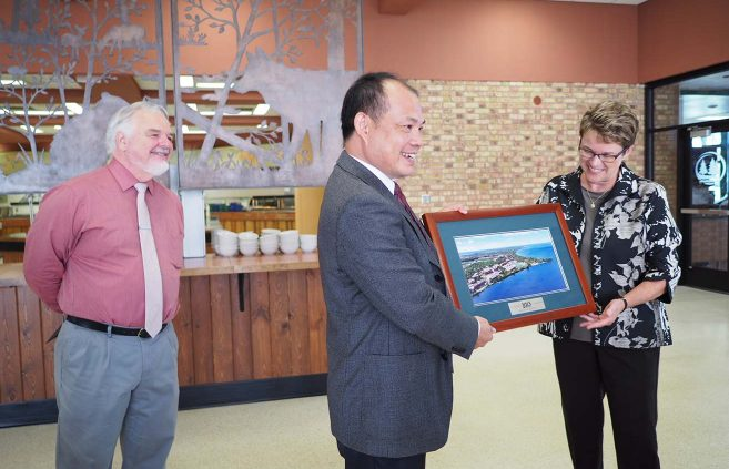 Tony Peffer (left), Shuai Shiyi and President Hensrud exchange gifts at a July 22 ceremony in Walnut Hall.