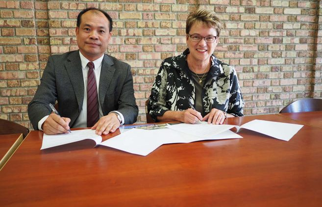 Shuai Shiyi and President Hensrud sign an agreement to pursue future faculty and student exchange opportunities.