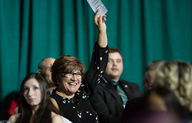Terri Thomas pledges in support of athletic scholarships during the live auction.