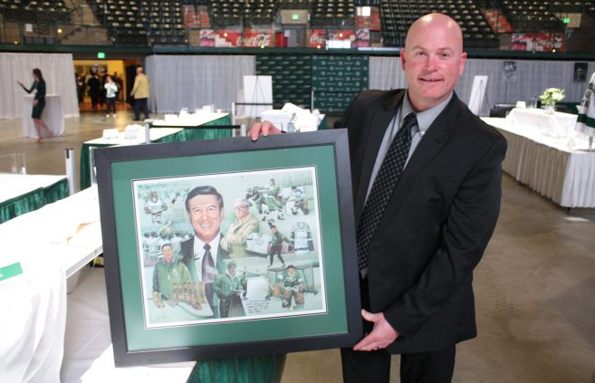 Vince Huerd poses with a commemorative print of his former coach, Bob Peters.