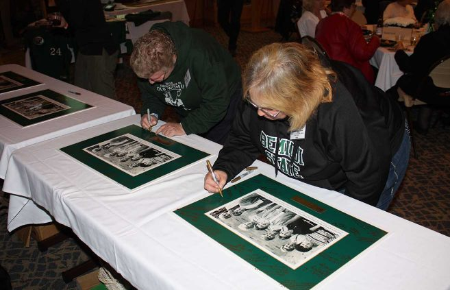 Alumnae add their signatures to photos presented to the Founders
