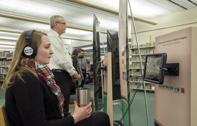 Bemidji State University faculty and staff viewing the Native Voices concept banners and using the installed iPads that feature video testimonials.