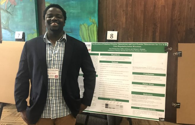 BSU student Dave-Preston Esoe with his project at the Minnesota State Undergraduate Scholars Conference.