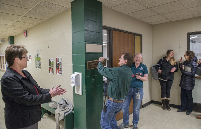 Wayne Robins and Lisa Skudlarek, general maintenance workers in Hagg-Sauer hall, removed the Arthur Lee Lecture Hall plaque from outside the classroom dedicated to the professor emeritus.
