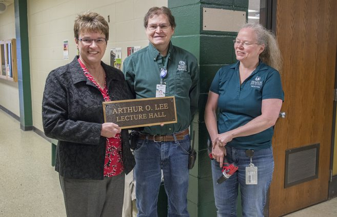 President Faith C. Hensrud with Wayne Robins and Lisa Skudlarek after the Arthur Lee Lecture Hall plaque was removed from outside the classroom dedicated to the professor emeritus.