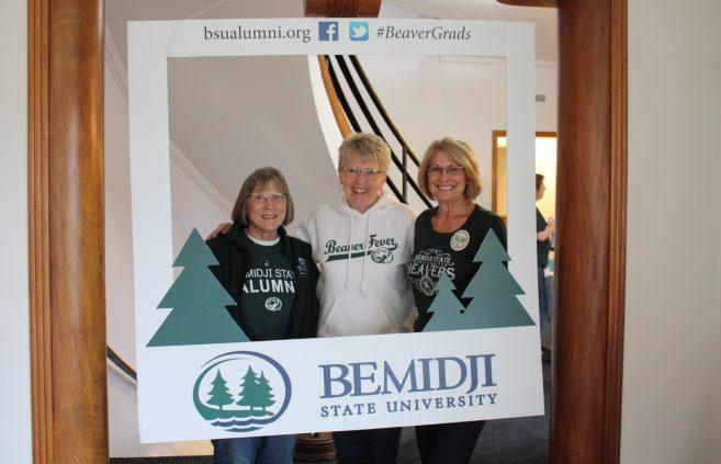 BSU alumni posing in the photo frame.