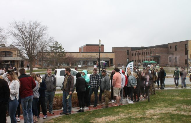 Students waiting for their senior send-off food and gift, despite the rainy weather.