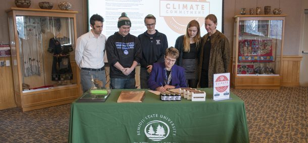President Faith Hensrud signs Second Nature's Climate Commitment