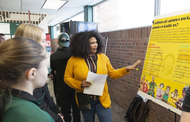 A student presenting her poster during the Student Achievement Conference