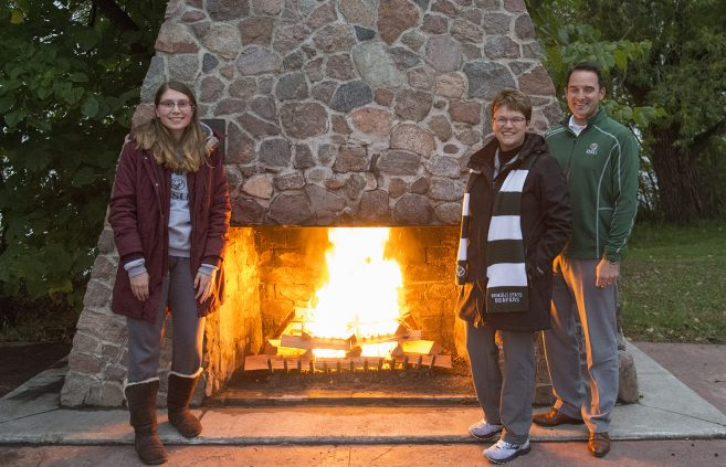 President Faith C. Hensrud, Josh Christianson, executive director of university advancement, BSU senior Abbie Newman in front of the fireplace.