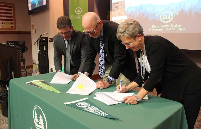 BSU and Pine Tech administrators sign a transfer agreement.
