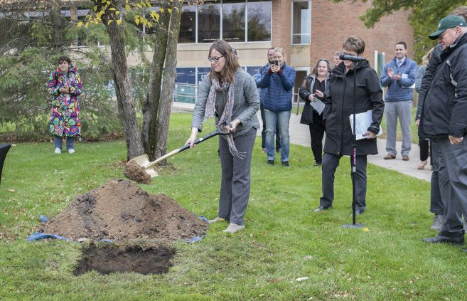 Colleen Deel shoveling dirt onto the 2019 time capsule