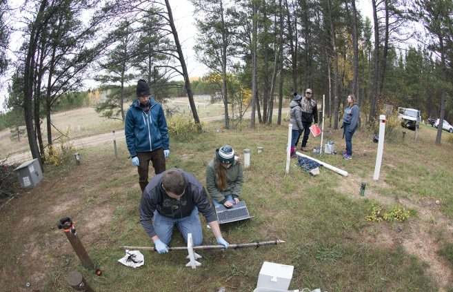 Bemidji State University students and faculty conducting research on microorganisms and oil degradation at an oil spill site near Pinewood, Minn.