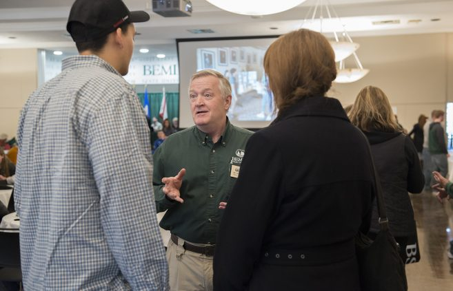 Dr. Mike Herbert of the criminal justice department speaks with visitors