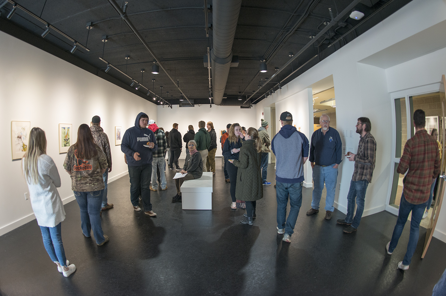 BSU students observing the paintings of Nikolay Aleksiev in the opening of the showcase.