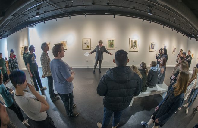 Natalia Himmirska, an associate professor in Bemidji State University's TAD School, introducing the work of Nikolay Aleksiev as her class visits the opening of the showcase.