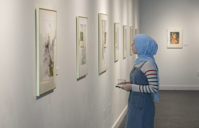 BSU student observing the paintings of Nikolay Aleksiev.