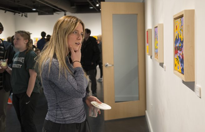 A student enjoys the art of Paul Swenson in BSU's Talley Gallery.
