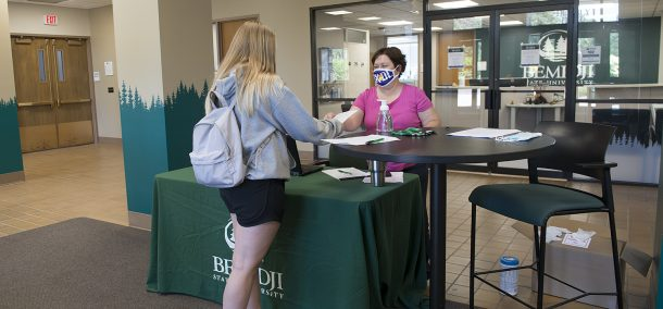 Gina Walkup from the BSU business office staffs the welcome table inside Deputy Hall, to ensure visitors complied with mask-usage guidelines and were completing the required online health screening survey. The station was open during the first few weeks of the Fall 2020 semester.