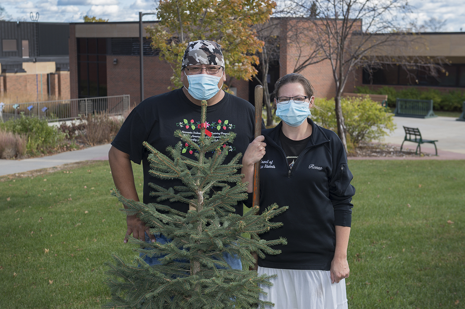 Renee Keezer with her husband, Justin,* *planting a tree on campus as a memorial to the legacy of Raymond and Margaret Carlson and their commitment to the welfare of future generations*.