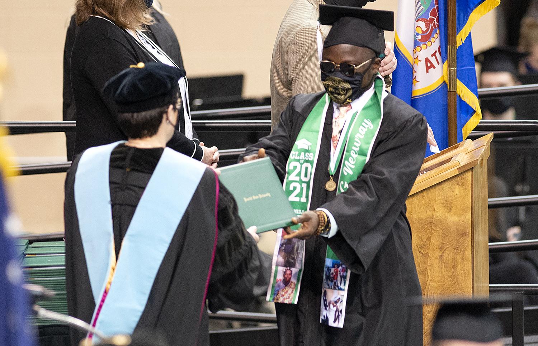 President Faith C. Hensrud confers a diploma