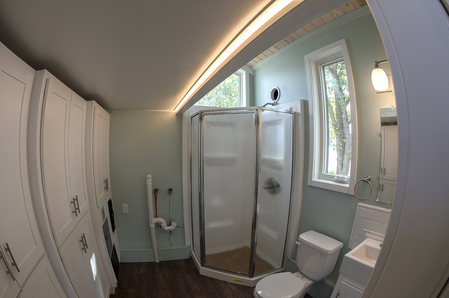 """Bemidji State University tiny house Three-quarter bathroom with 32"""" Stylemate Neo Angle shower enclosure, ProFlo flush toilet prewired for an optional composting toilet and full-height storage cabinets."""
