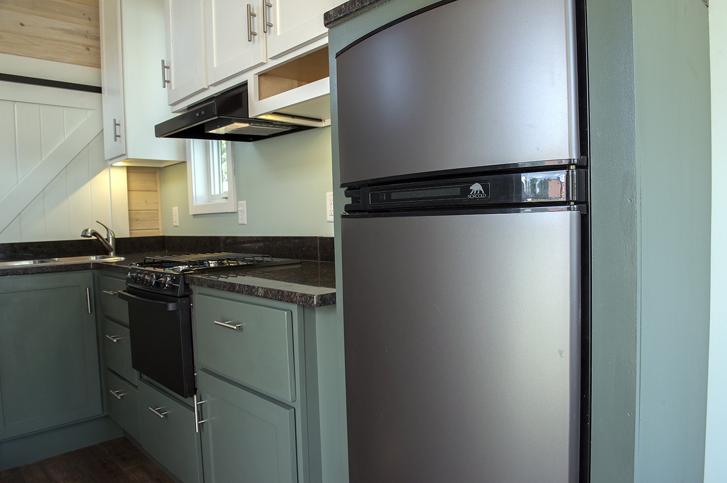 Bemidji State University tiny house Norcold gas/electric refrigerator, full-height kitchen cabinets, granite countertops, Atwood LP gas range and slide-in cooktop.