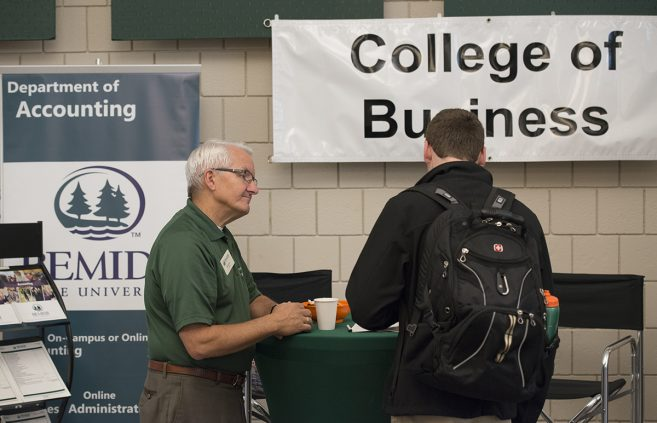 Dr. William Graves from the Accounting department providing information to a student at the Major & Career Expo