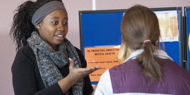 Student Employee sharing information with a fellow student at the Major & Career Expo